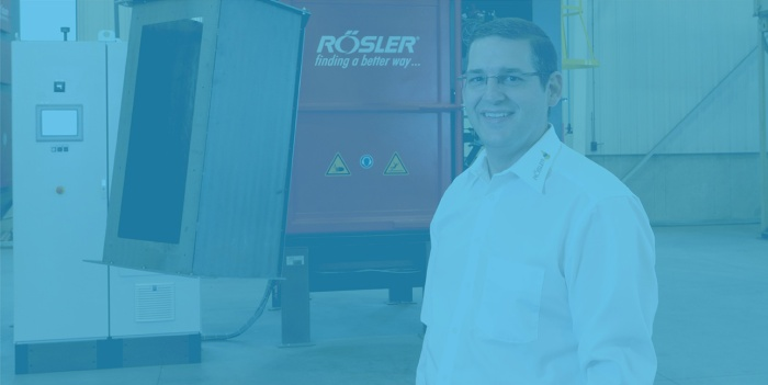 Bernie Kerschbaum smiles in front of a sign for Rosler Metal Finishing USA in Battle Creek, Michigan.