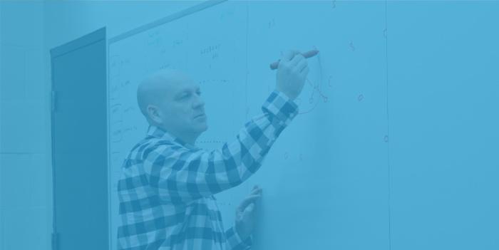 Coach Granger writes on a whiteboard at Battle Creek Central High School.