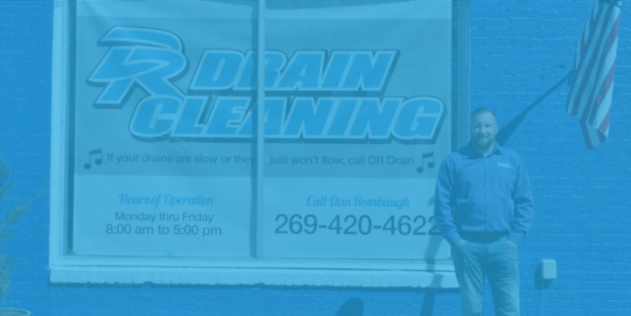 An image of Dan Rombaugh standing in front of a drain cleaning sign.